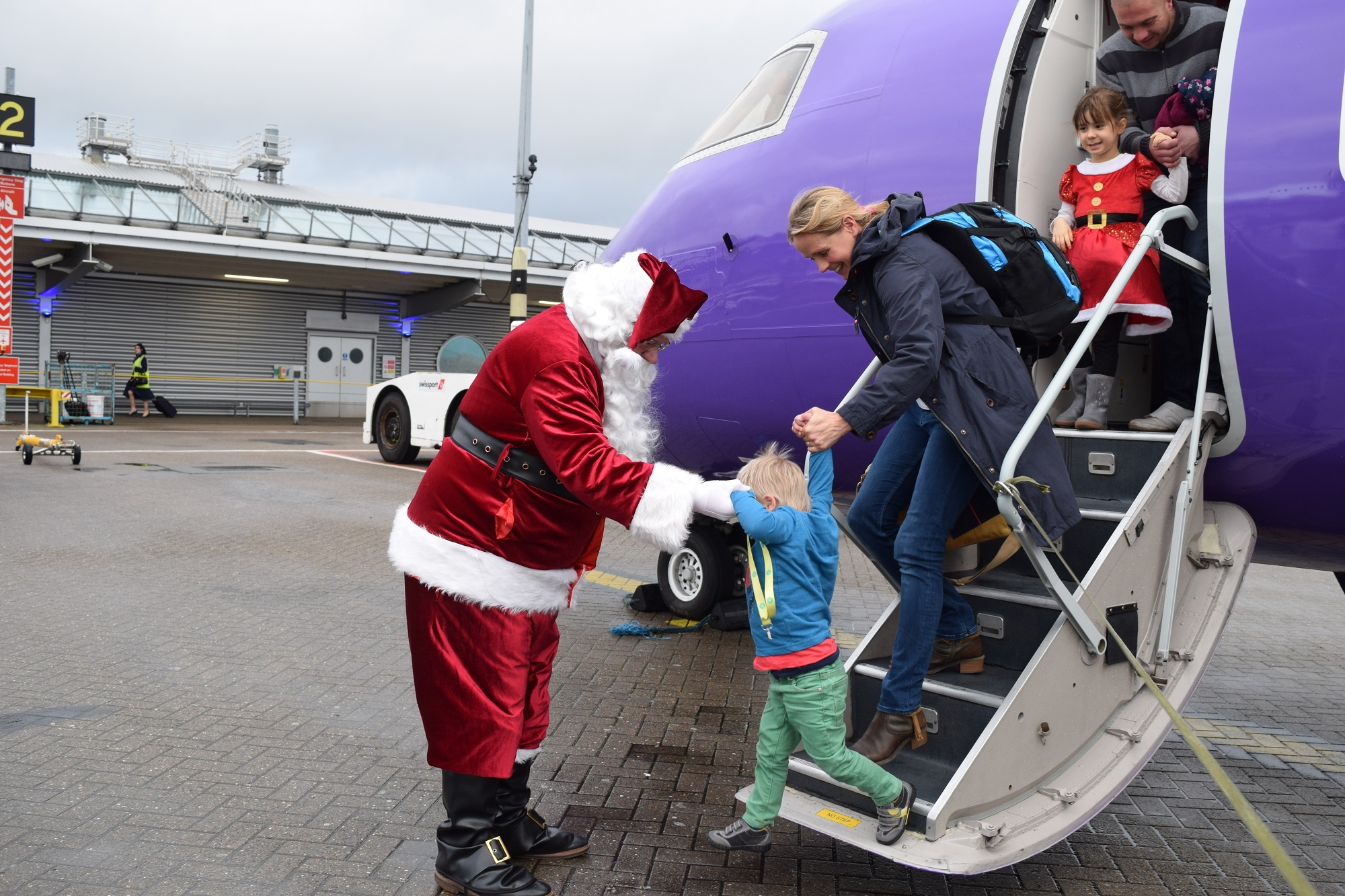 Santa helping the children arrive from their Santa Flight at Southampton Airport with Flybe